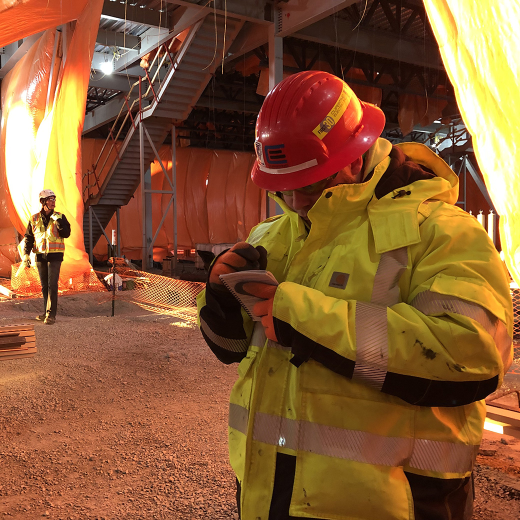 A man wears a yellow safety jacket and red hard hat and writes in a small notebook.